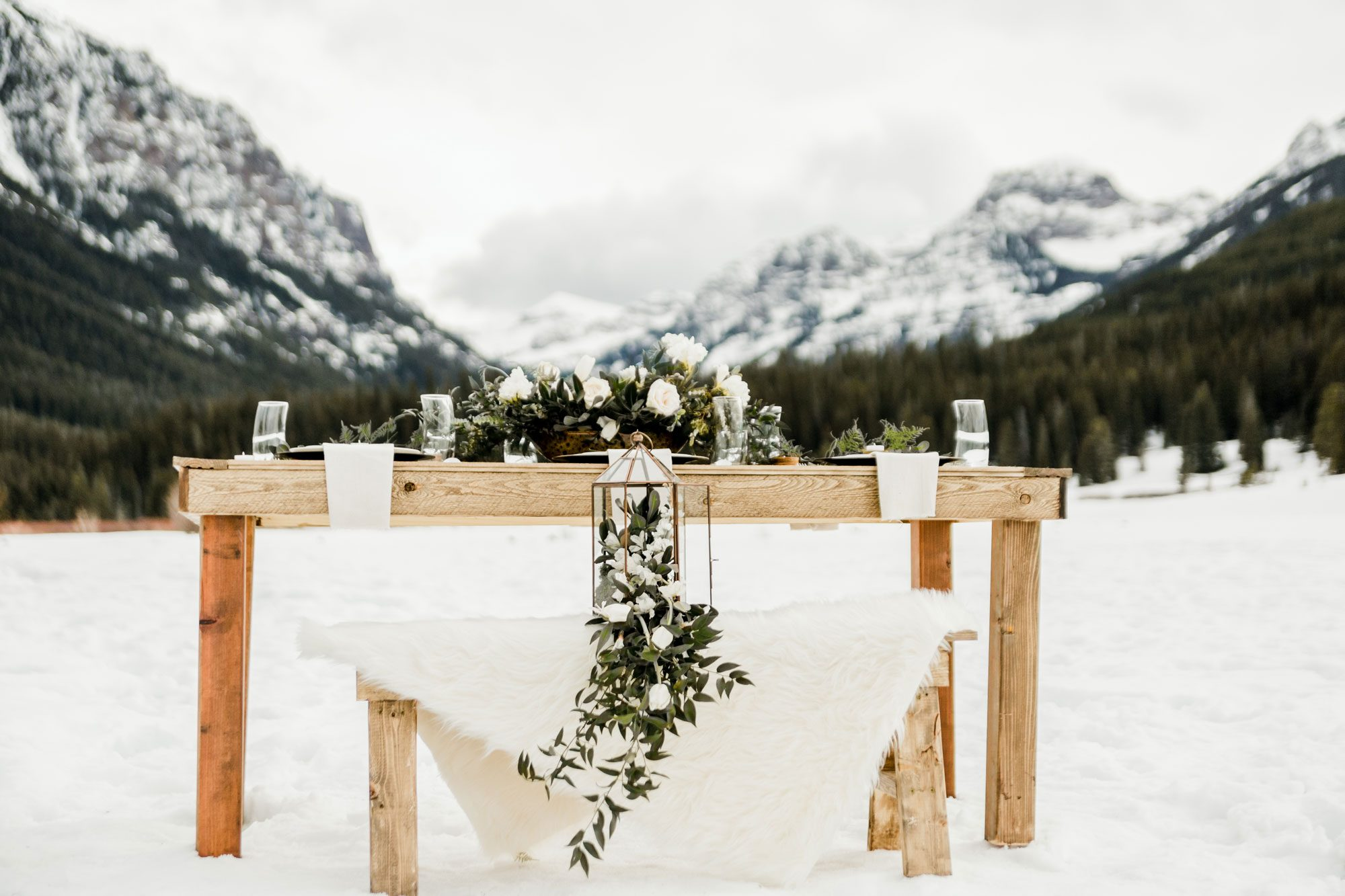 A winter tablescape in the mounatins with wood, metal, white florals & greenery accents