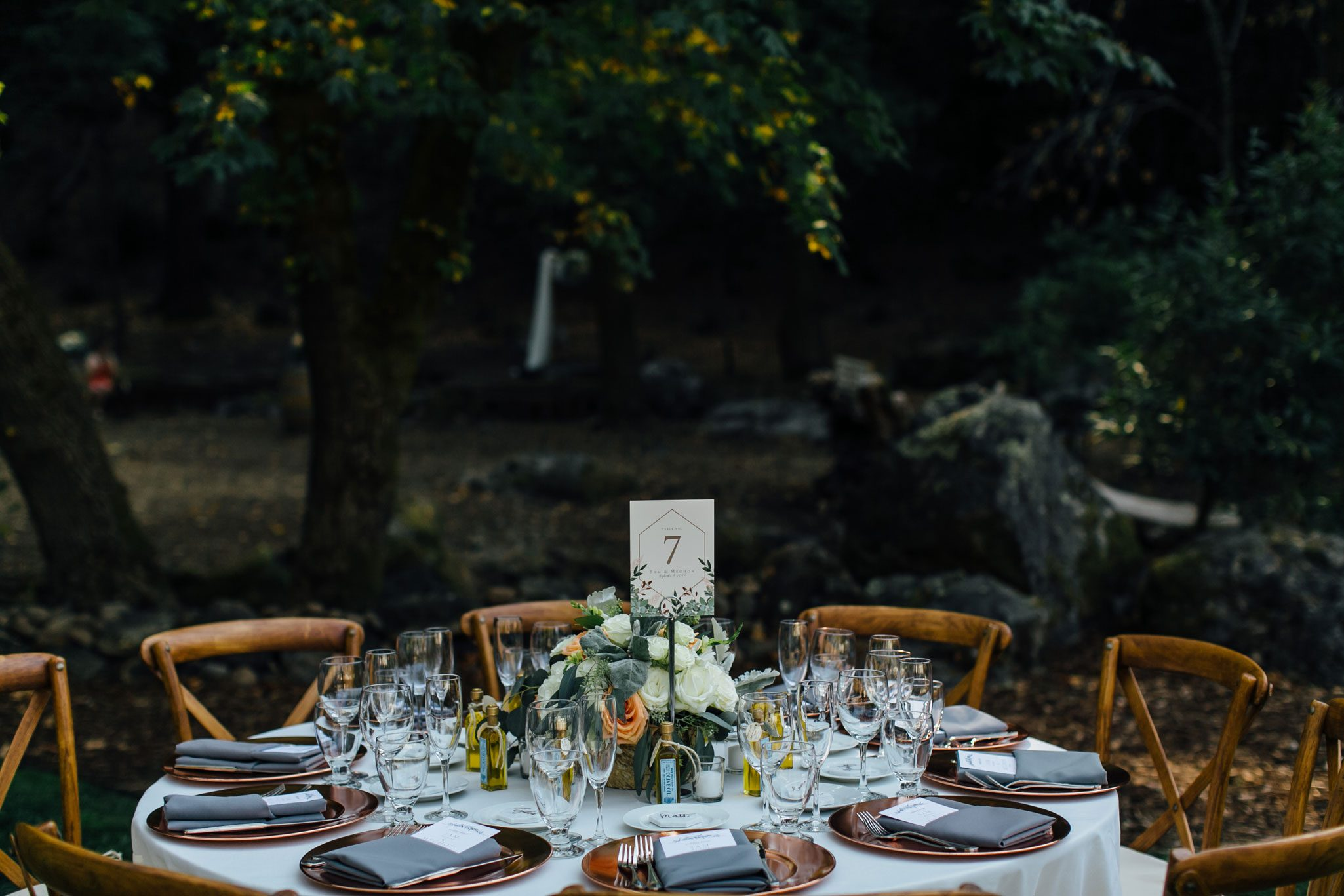 Tablescape with solid ivory table linen and grey napkins, and copper chargers