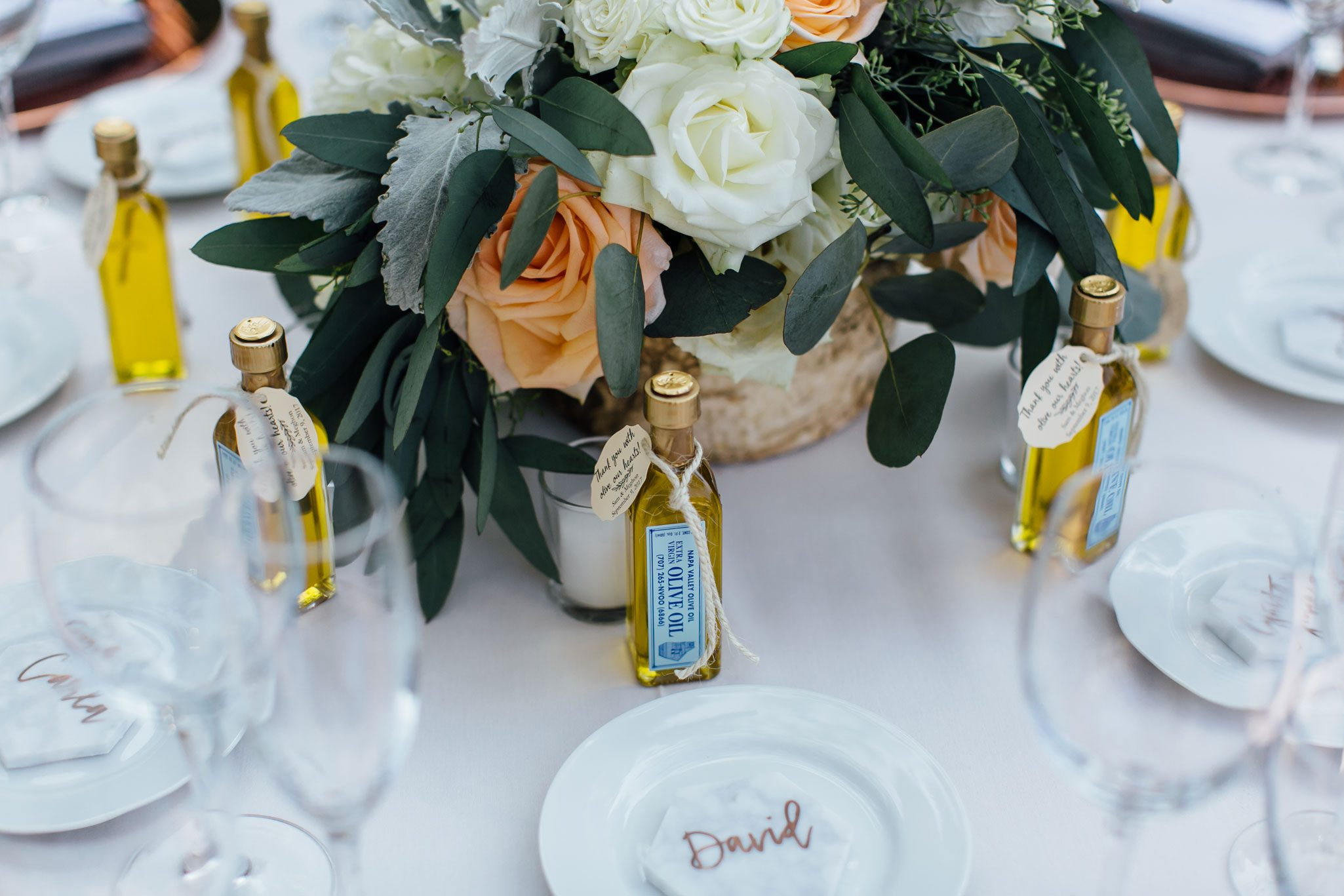 Tablescape with solid ivory table linen and grey napkins, olive oil favor, and copper chargers