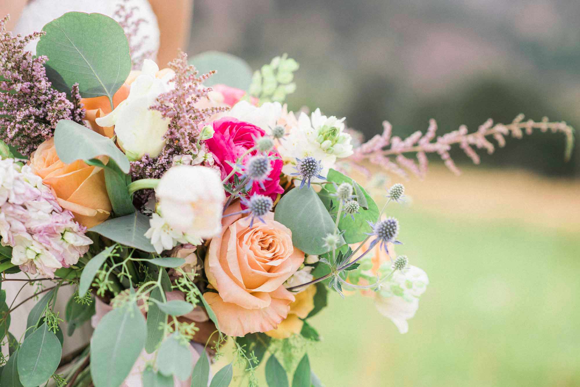 Organic wedding bouquet overflowing with coral, golden, and fuchsia roses in Boulder, Colorado