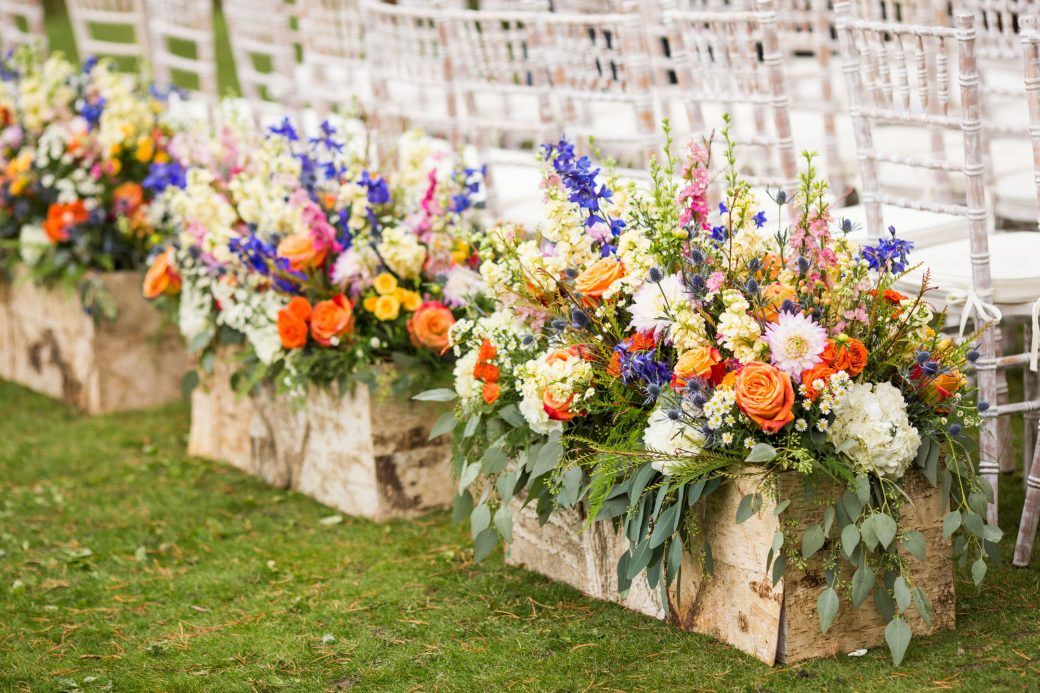 Lush floral arrangements at the back of the ceremony aisle | Luxe Mountain Weddings