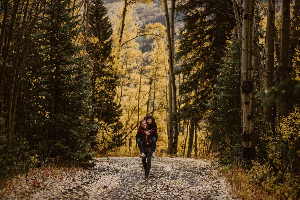 Engaged couple walking down a mountain road covered in fall aspen leaves
