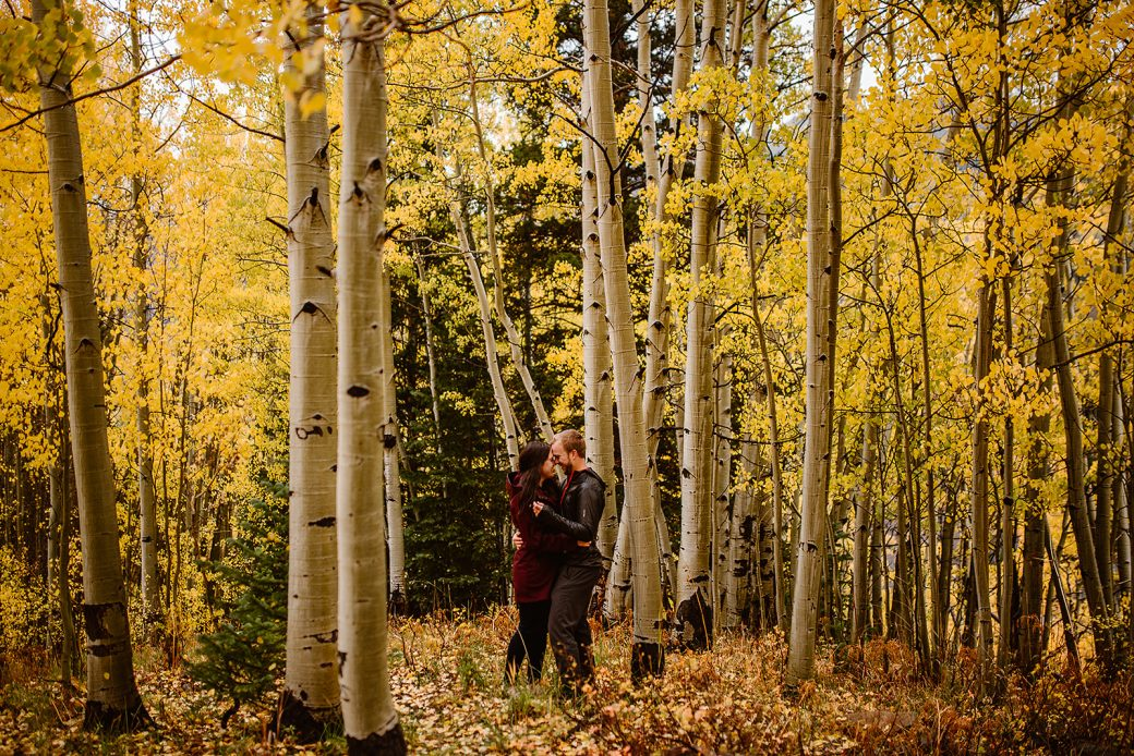 Engaged couple playing in the fall leaves