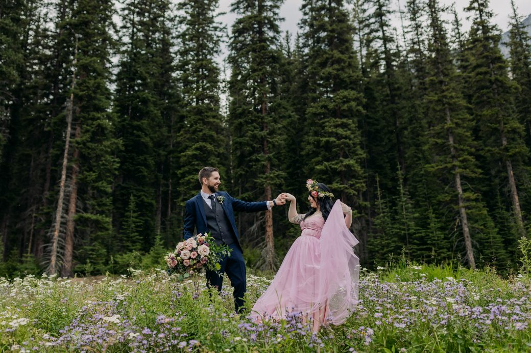 Bride and groom dancing in wildflower field.