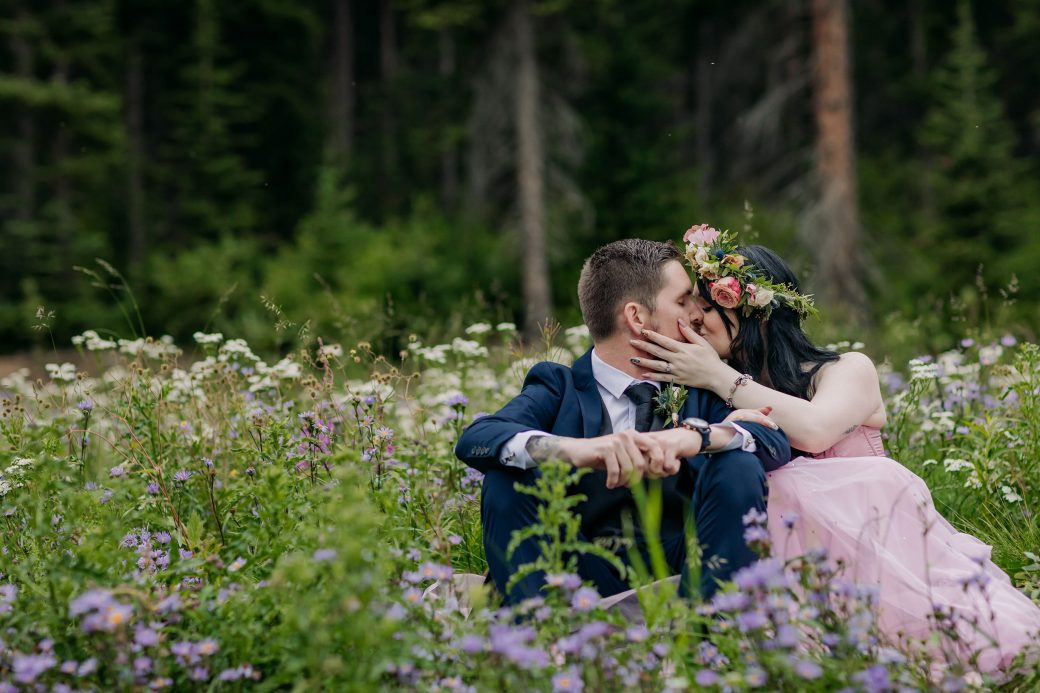 Bride and groom kissing in wildflower field.
