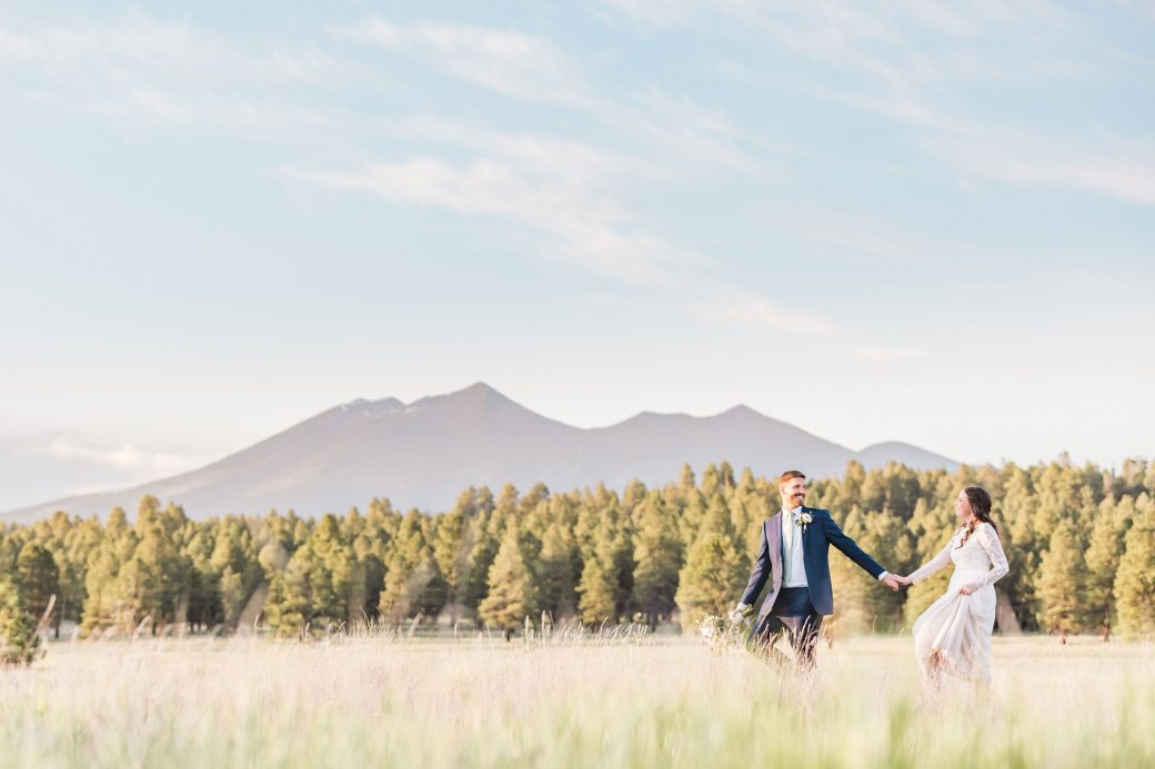 A newly married couple running at the edge of a Ponderosa Pine Forest with the majestic Mount Humphreys in the background in Flagstaff, Arizona